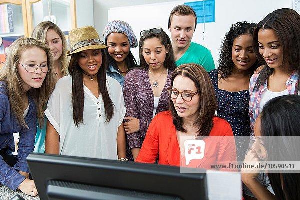 Lehrerin  die den Schülern den Computer zeigt