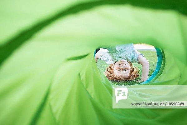 Kleiner Junge  auf dem Kopf stehend  durch die Spielröhre im Garten schauend