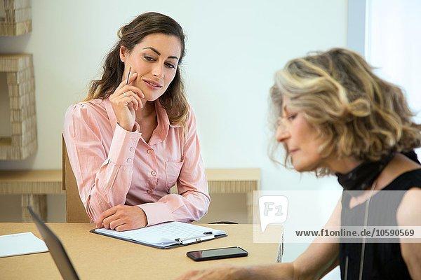 Zwei Geschäftsfrauen beim Brainstorming am Vorstandstisch
