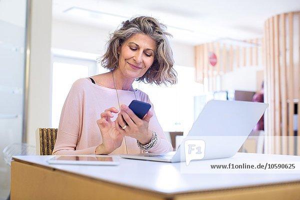 Porträt der Senior-Designerin beim Texten auf dem Smartphone im Büro