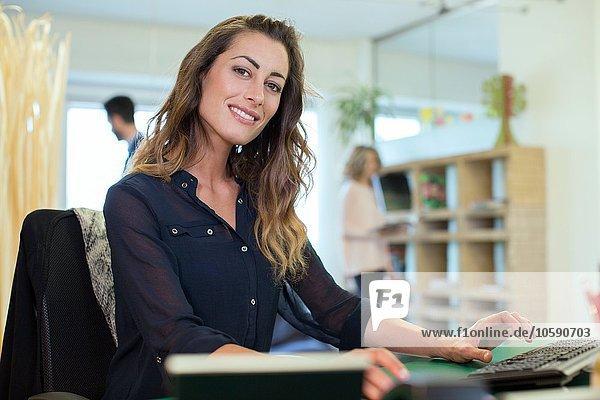 Porträt einer jungen Geschäftsfrau am Schreibtisch