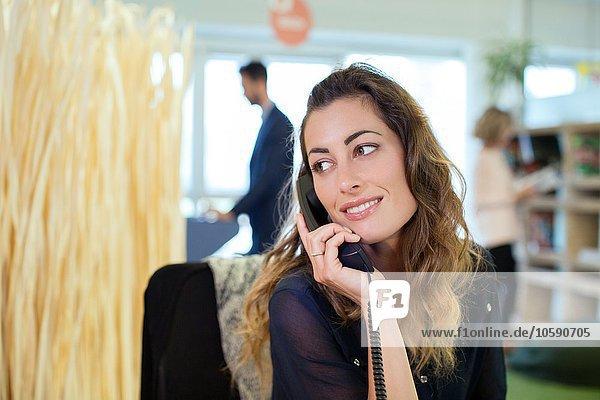 Junge Geschäftsfrau im Büro am Festnetztelefon