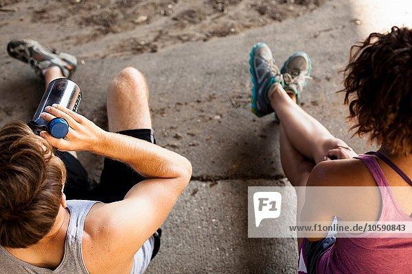 Overhead-Ansicht von Joggern  die auf der Bordsteinkante Pause machen