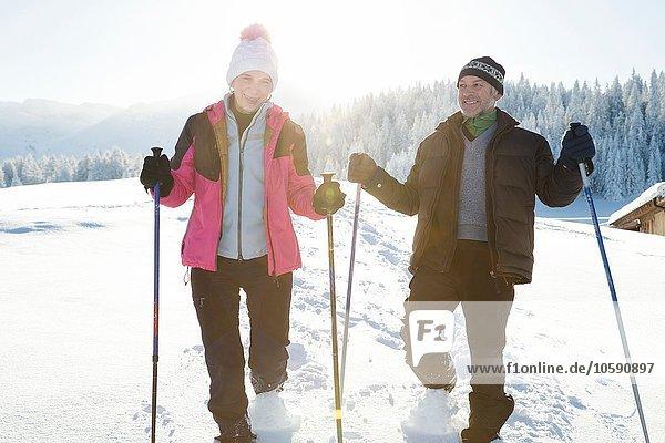 Vorderansicht des Seniorpaares auf verschneiter Landschaft mit Wanderstöcken  Sattelbergalm  Tirol  Österreich
