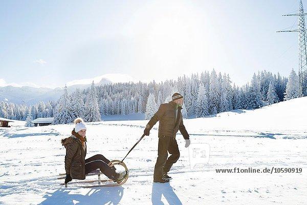 Seitenansicht des älteren Mannes gezogene ältere Frau auf Schlitten  Sattelbergalm  Tirol  Österreich