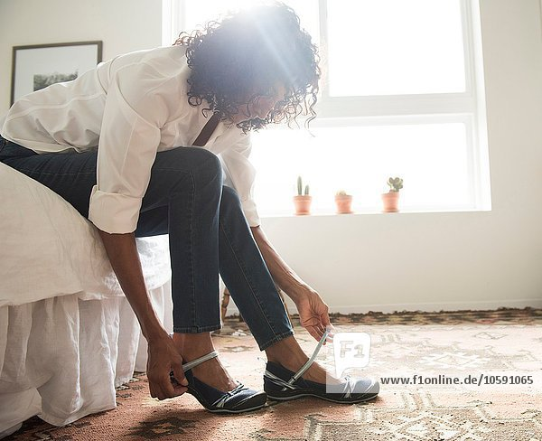 Mature woman sitting on bed putting on shoes