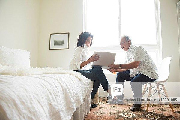 Senioren-Paar mit Blick auf Laptop im Schlafzimmer