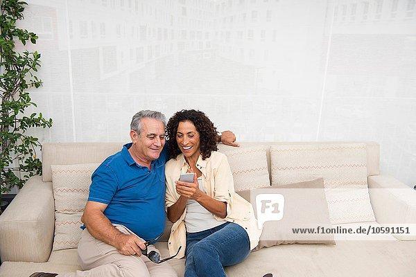 Senior Mann und Frau lesen Smartphone-Texte auf der Terrasse Sofa