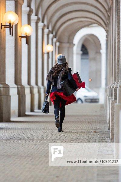 Rückansicht der reifen Frau mit Weihnachtsgeschenk beim Spaziergang durch die Stadtkolonnade