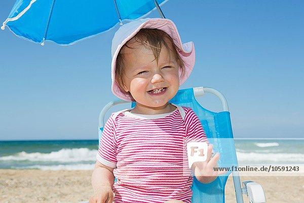 Kleinkind mit Sonnenhut auf Strandkorb