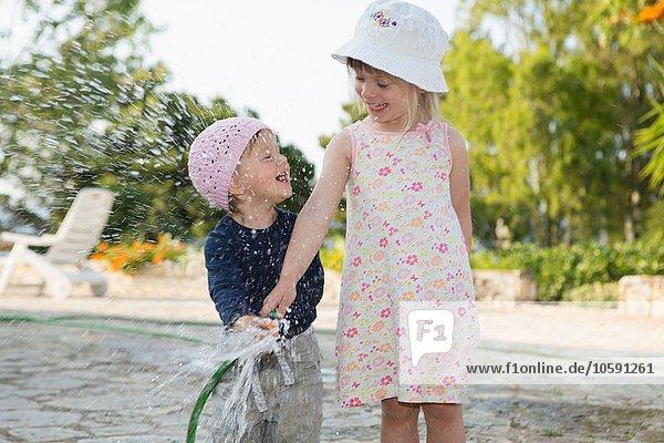 Mädchen und Kleinkindschwester spielen mit Wasserschlauch im Garten Mädchen und Kleinkindschwester spielen mit Wasserschlauch im Garten