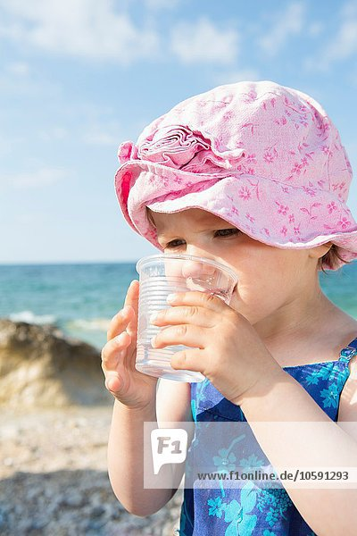 Weibliches Kleinkind Trinkwasser am Strand