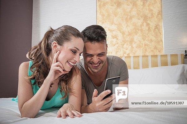Junges Paar liegt auf dem Bett und liest Smartphone-Text im Hotelzimmer.