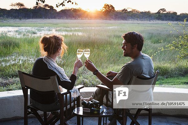 Weintoast bei Sonnenuntergang in der Safari Lodge  Kafue National Park  Sambia