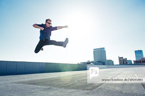 Geschäftsmann beim Flying Kick auf der Dachterrasse  Los Angeles  Kalifornien  USA