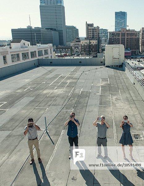 Geschäftsleute fotografieren mit Smartphones auf der Dachterrasse  Los Angeles  Kalifornien  USA