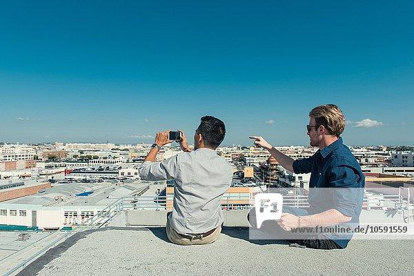 Geschäftsleute fotografieren mit Smartphone auf der Dachterrasse  Los Angeles  Kalifornien  USA