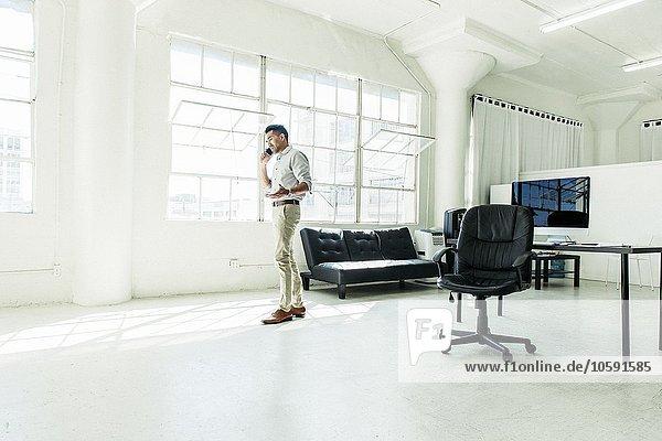 Geschäftsmann beim Sprechen auf dem Smartphone am Bürofenster