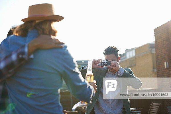 Junger Mann fotografiert männliche Freunde auf der Dachparty