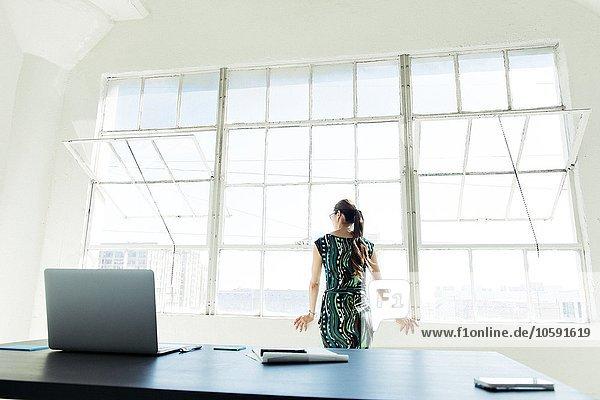 Geschäftsfrau mit Blick aus dem Bürofenster