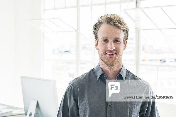 Lächelnder Geschäftsmann am Bürofenster