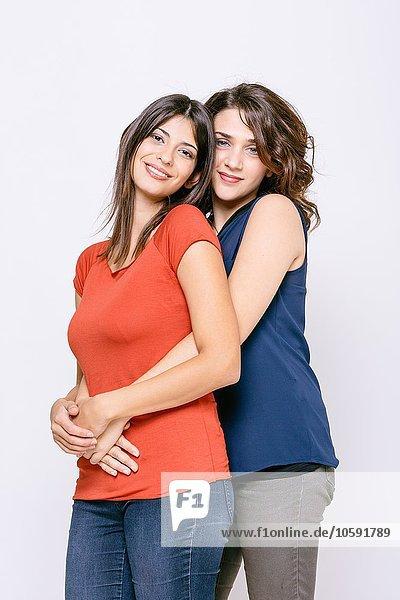 Lesbisches Paar steht umarmt und schaut lächelnd in die Kamera.