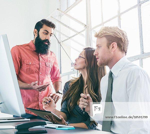 Geschäftsleute im Brainstorming Meeting durch das Bürofenster