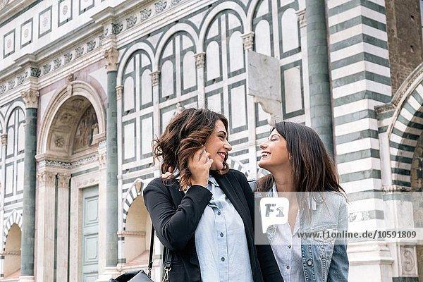Lesbisches Paar mit Handy von Angesicht zu Angesicht lächelnd  Piazza Santa Maria Novella  Florenz  Toskana  Italien