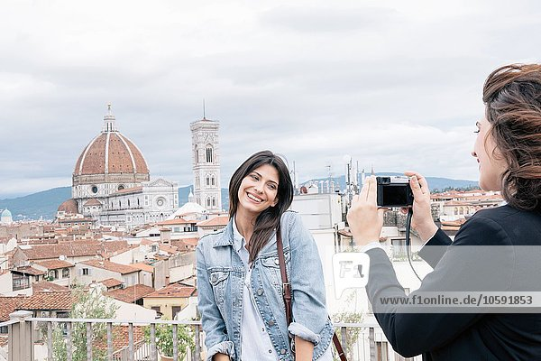 Junge Frau,  die für einen Freund posiert und vor der Kathedrale von Florenz und dem Campanile von Giotto fotografiert,  lächelnd über die Schulter schaut,  Florenz,  Toskana,  Italien