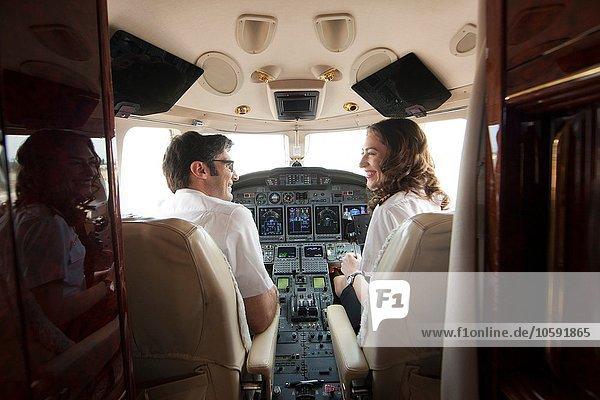 Rückansicht des männlichen und weiblichen Piloten im Cockpit des Privatjets