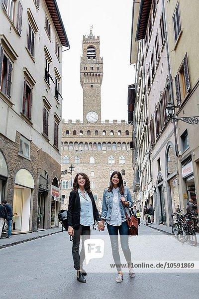Tiefblick auf ein lesbisches Paar  das in der Straße unter dem Palazzo Vecchio steht und Händchen hält  Florenz  Toskana  Italien