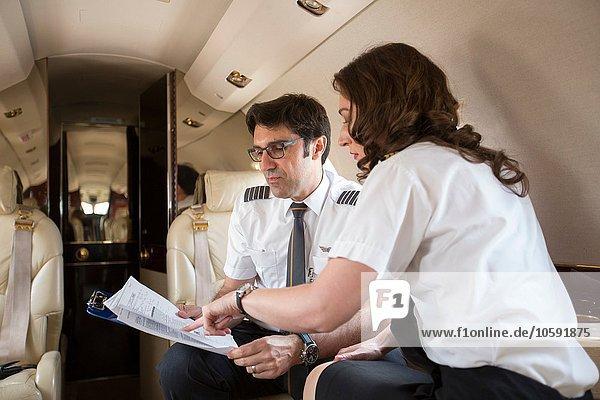 Pilotinnen und Piloten beim Lesen des Flugplans in der Kabine des Privatjets