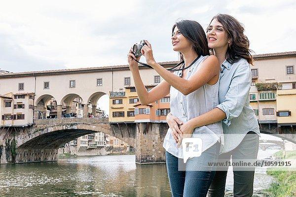 Lesbisches Paar  das vor der Ponte Vecchio und dem Fluss Arno steht und mit Digitalkamera fotografiert  Florenz  Toskana  Italien