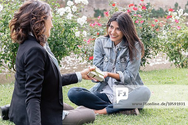 Lesbian couple sitting on grass giving  receiving gift  Florence  Tuscany  Italy