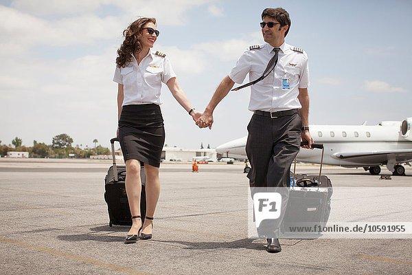 Privatjetpiloten und Privatpiloten  die am Flughafen Händchen halten
