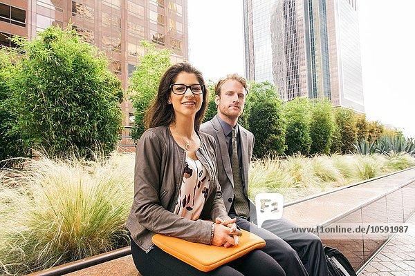 Geschäftsmann und Frau an der Wand sitzend mit Laptop in der Stadt
