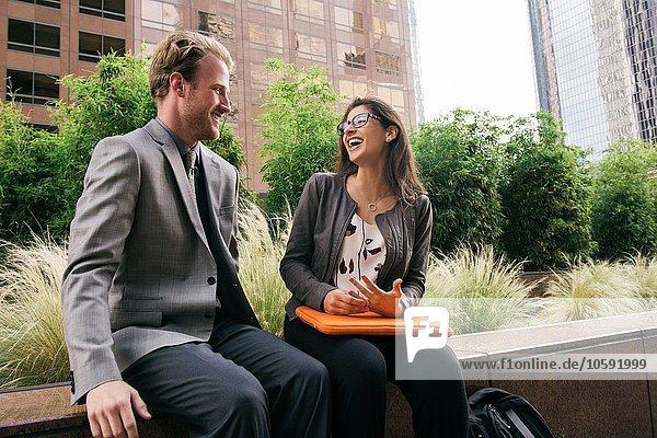 Geschäftsmann und Frau in der Stadt auf der Mauer sitzend redend