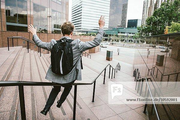 Geschäftsmann  der den Treppenhandlauf herunterrutscht  Los Angeles  USA