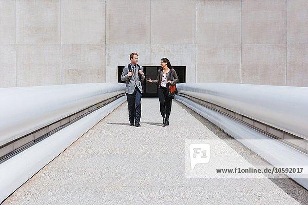 Geschäftsmann und Frau im Gespräch auf dem Stadtbummel