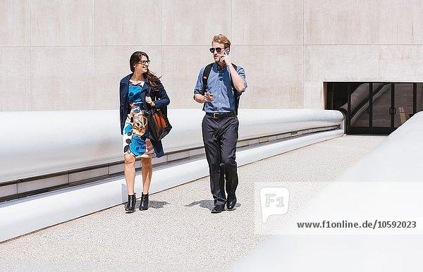 Geschäftsmann und Frau gehen und reden in der Stadt