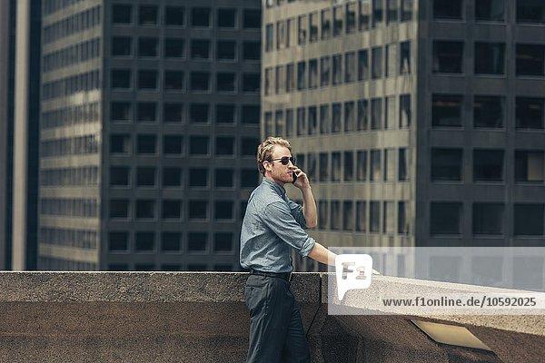 Geschäftsmann im Gespräch auf dem Smartphone vom Dach  Los Angeles  USA