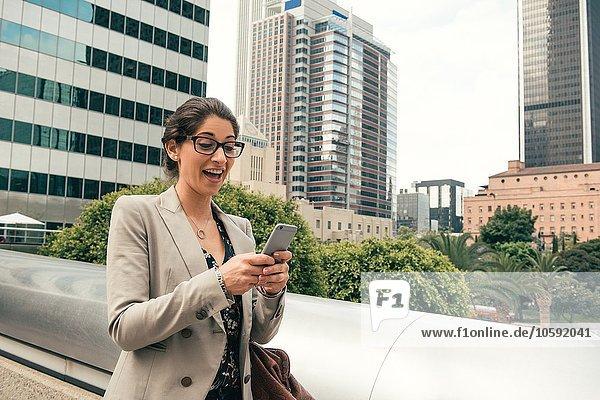 Geschäftsfrau beim Lesen von Smartphone-Texten von footbridge  Los Angeles  USA