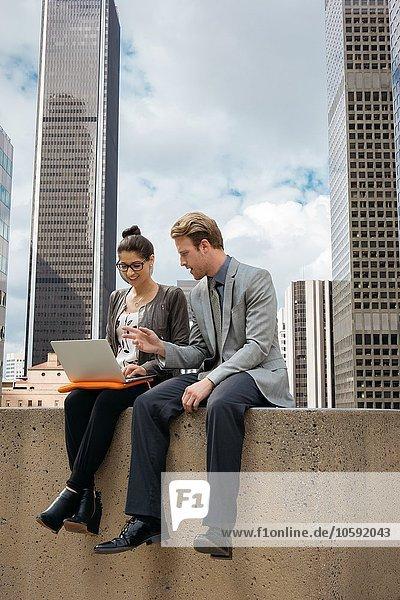Geschäftsmann und Frau mit Laptop an der Wand  Los Angeles  USA