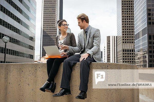 Geschäftsmann und Frau an der Wand sitzend mit Laptop  Los Angeles  USA