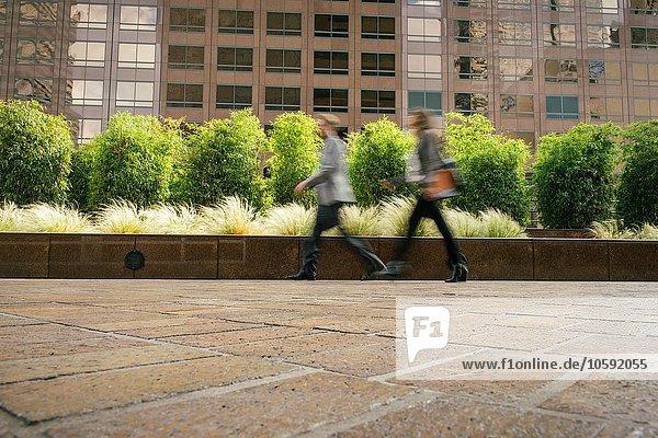 Geschäftsmann und Frau  die eilig vor Bürogebäuden herumlaufen