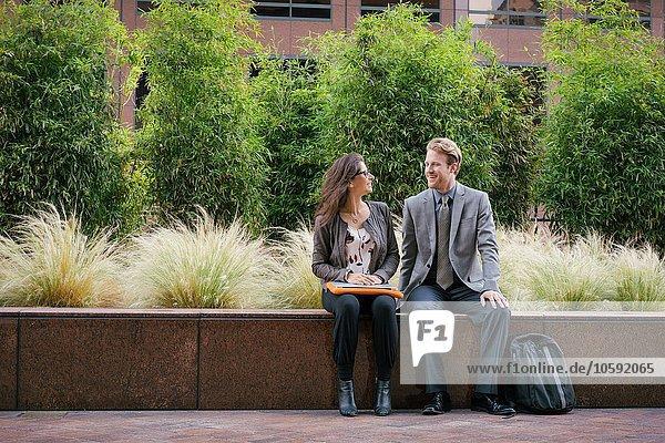 Geschäftsmann und Frau in der Stadt  die auf der Wand sitzen und plaudern