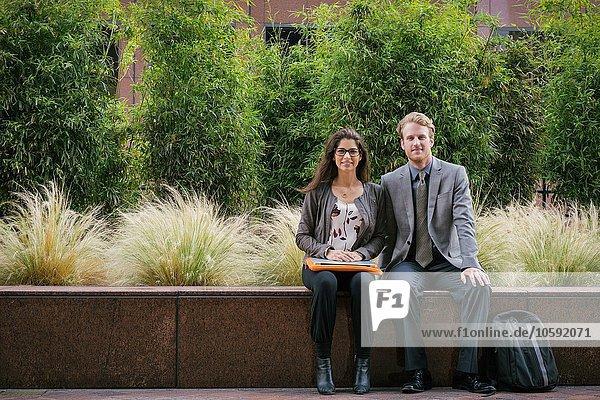 Geschäftsmann und Frau in der Stadt sitzend auf der Wand mit Laptop