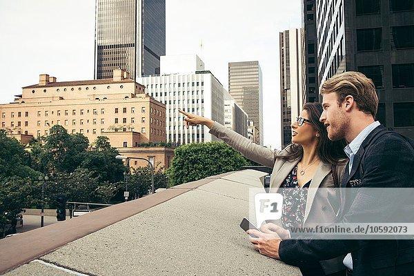 Geschäftsmann und Frau  die vom Gehweg aus  Los Angeles  USA  zeigen.