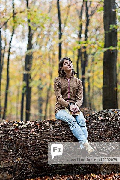Mädchen träumt auf Baumstamm im Herbstwald