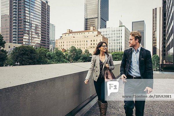 Geschäftsmann und -frau beim Spazierengehen und Reden in der Stadt  Los Angeles  USA